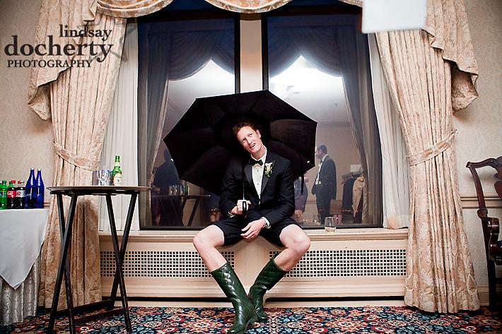fun groomsman with umbrella