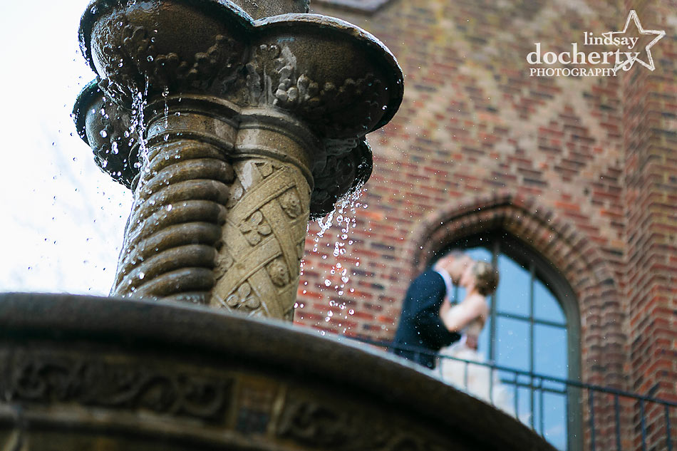 Bride and groom kiss at Aldie Mansion fountain
