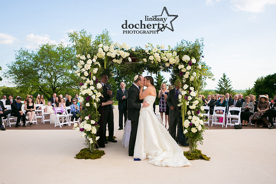 Jewish wedding kiss under huppah at ACE Conference Center in Lafayette Hill