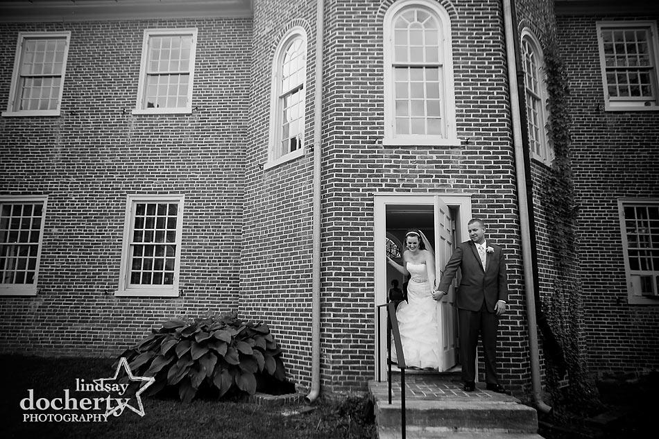 bride and groom hold hands around door before ceremony