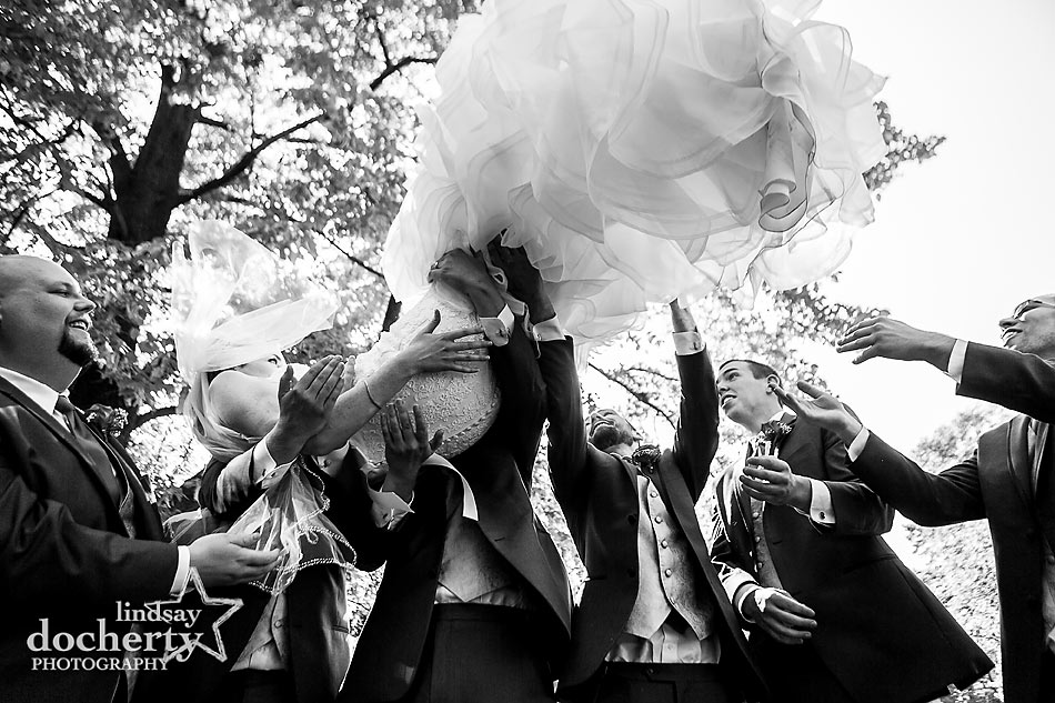groomsmen tossing bride in air with frilly dress