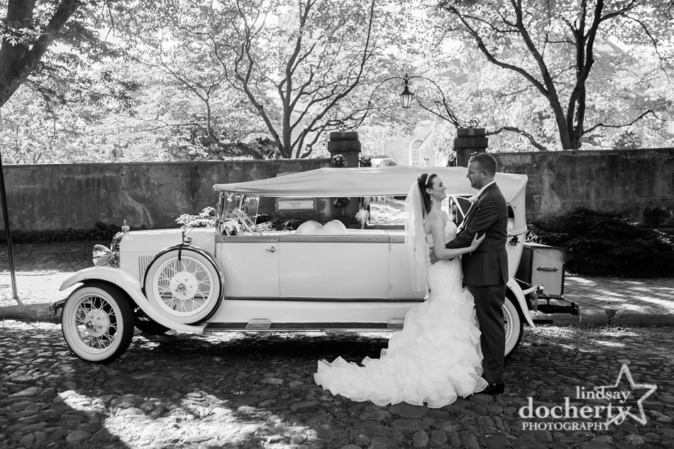wedding couple in front of vintage limo