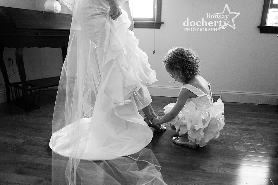 flower girl helping bride with shoe on wedding day