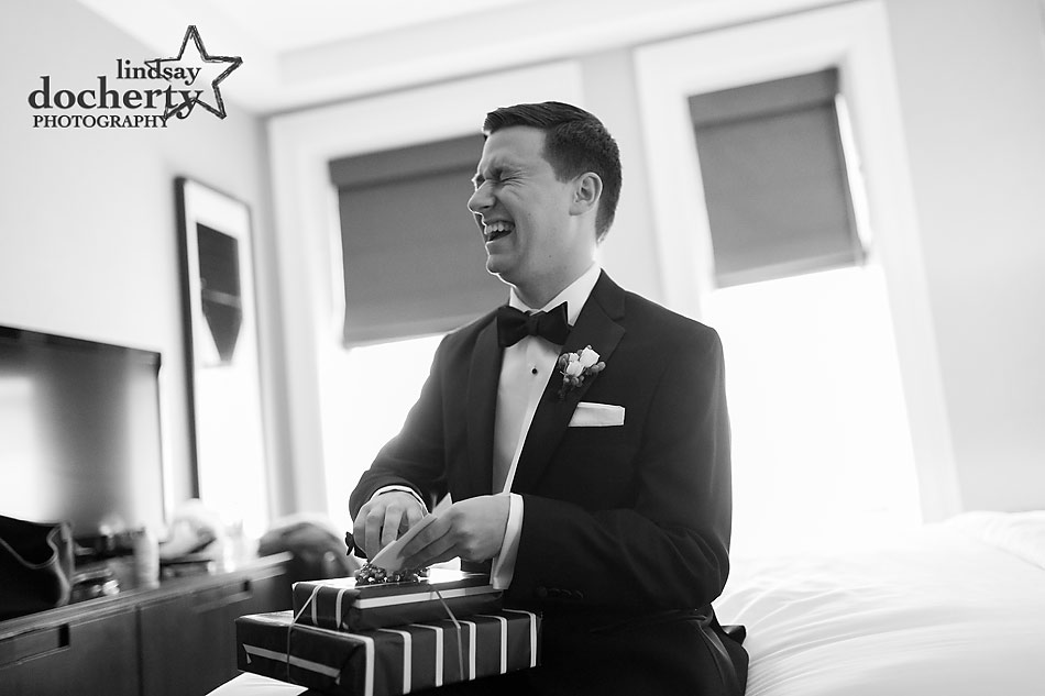 groom laughing upon getting a gift from bride
