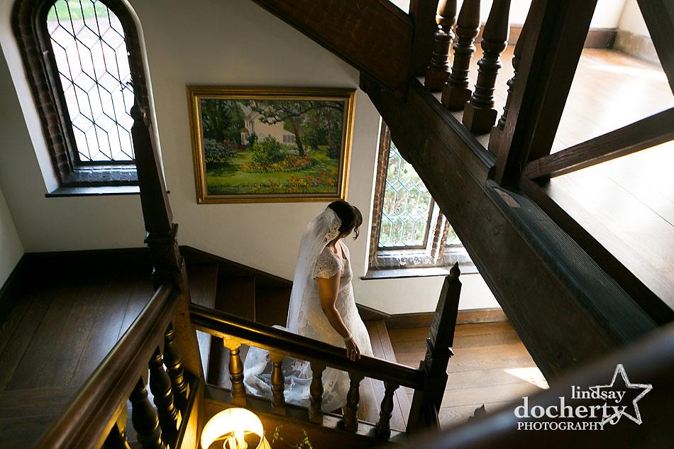 bride walking down stairs to see groom at Aldie Mansion wedding in Doylestown