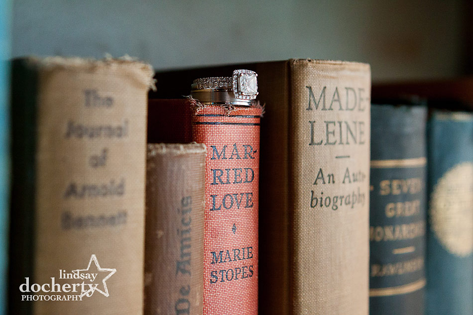 wedding and engagement rings on old books in library at Aldie Mansion wedding in Doylestown
