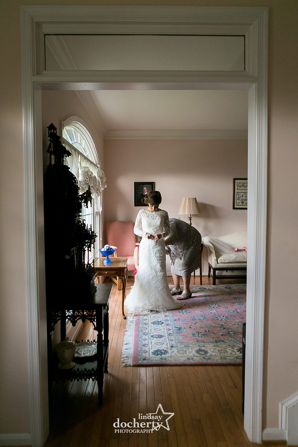bride in long sleeved dress getting ready at home the morning of the wedding