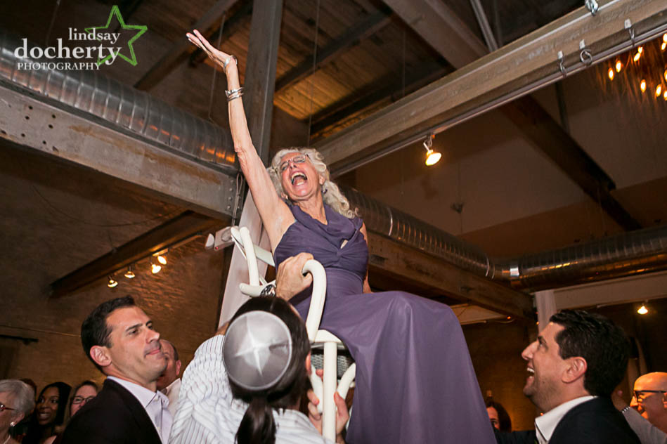 mother on chair during hora at Jewish wedding