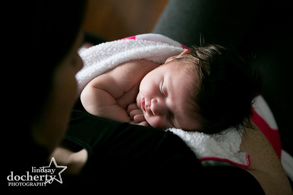 sleepy newborn little girl in mom's arms