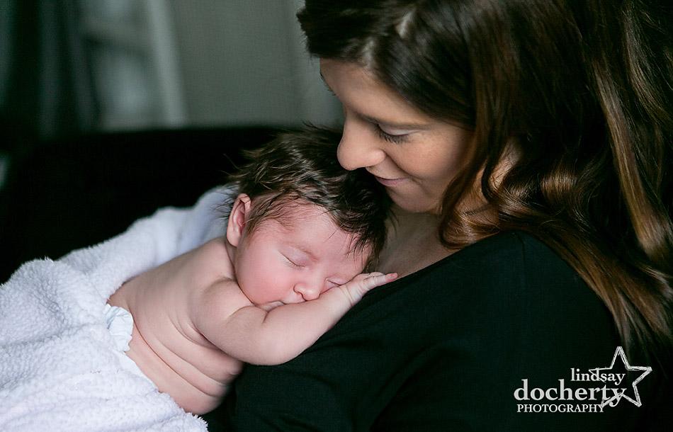 sleepy newborn little girl on mom's chest