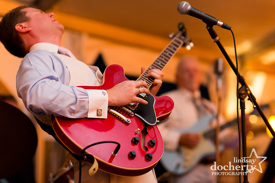 groom playing guitar to wife during tented wedding reception on Shelter Island, NY
