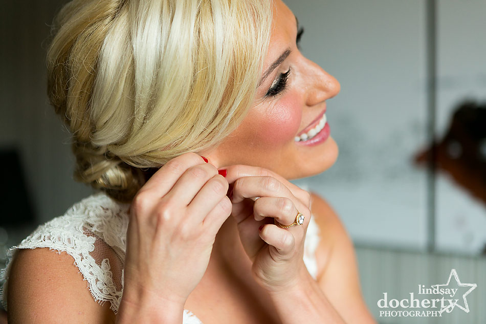 beautiful-blonde-bride-putting-on-earrings