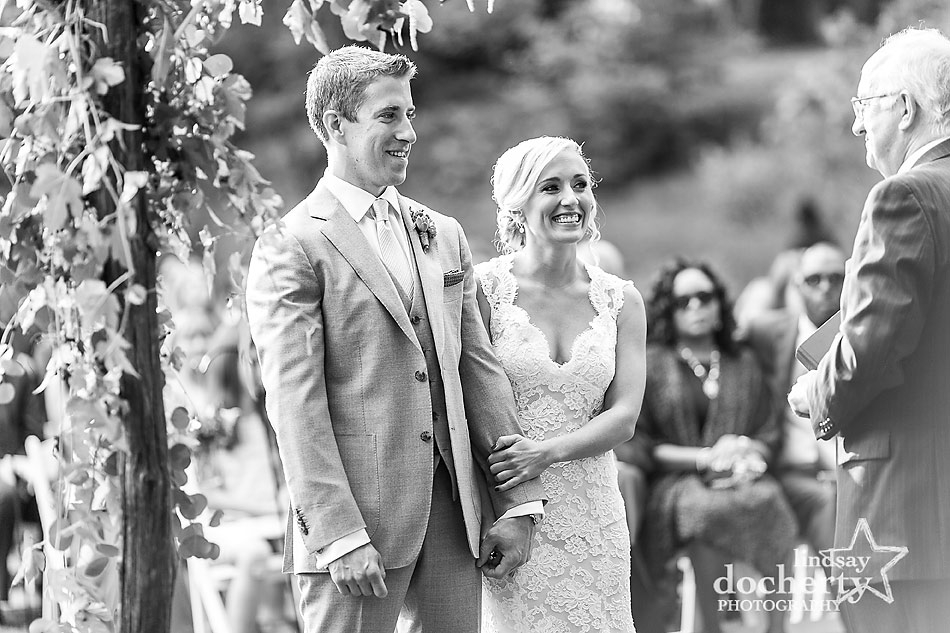 bride-and-groom-smiling-during-wedding-ceremony-at-fall-wedding-at-Tyler-Arboretum