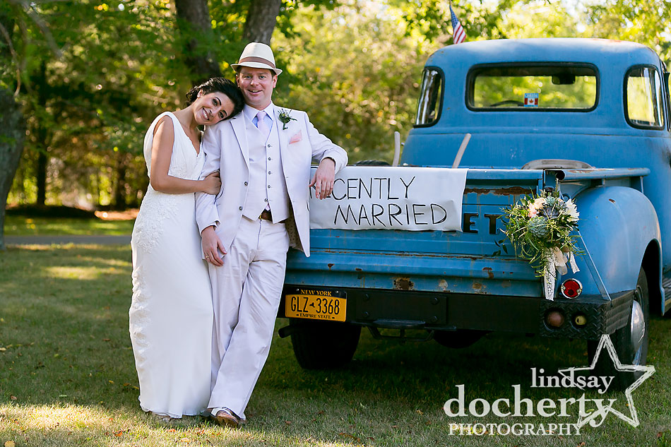 bride and groom with blue pickup truck at backyard wedding on Shelter Island in New York