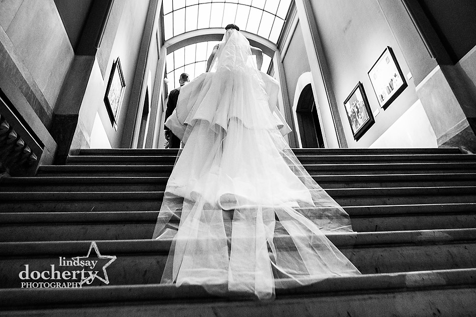 bride with long veil and groom walking up stairs at wedding at PAFA in Philadelphia