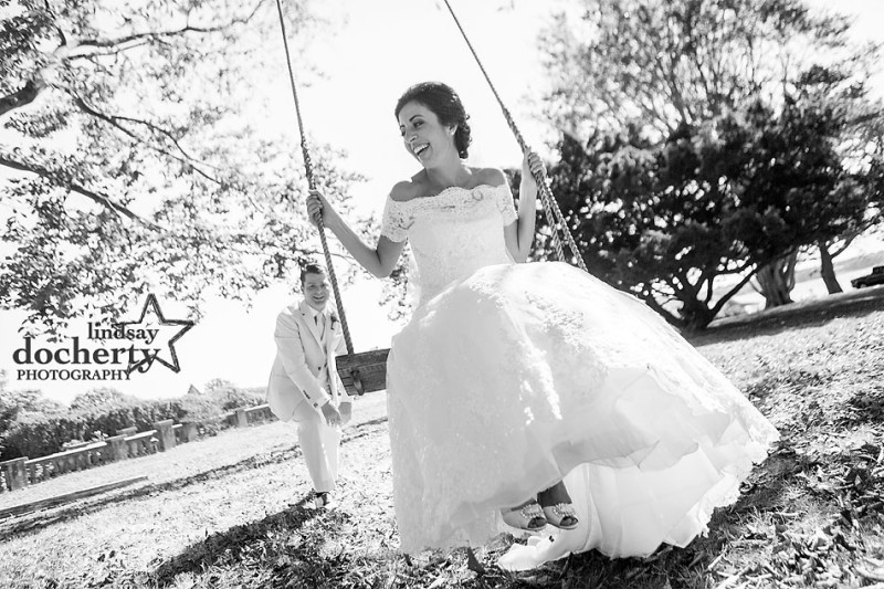 bride and groom on swings at backyard wedding on Shelter Island in New York