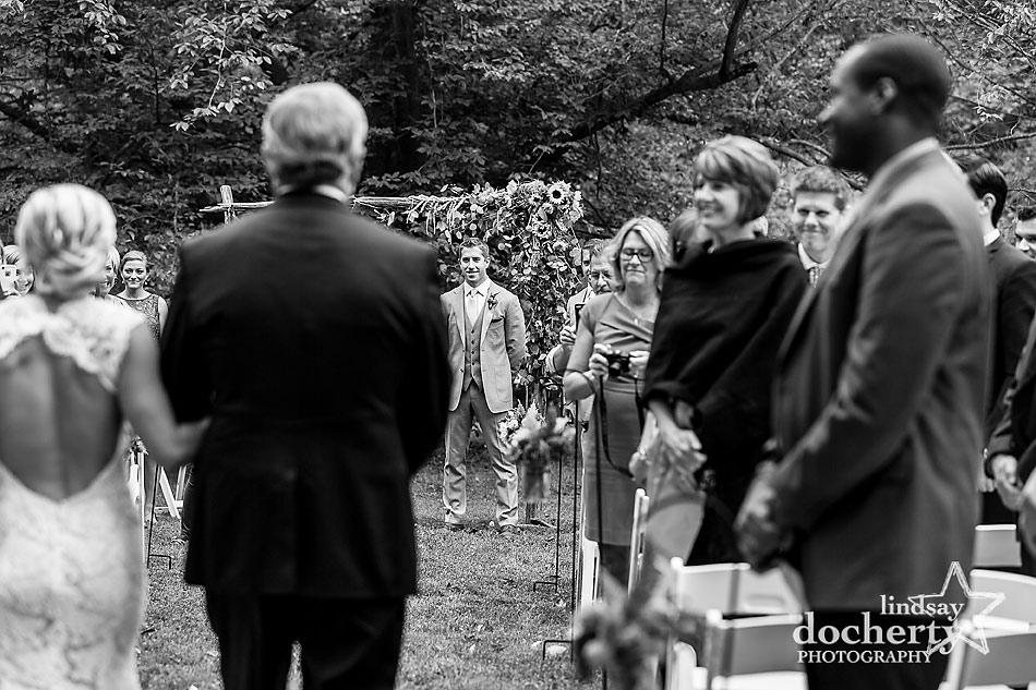 bride-walking-down-aisle-toward-groom-at-fall-wedding-at-Tyler-Arboretum