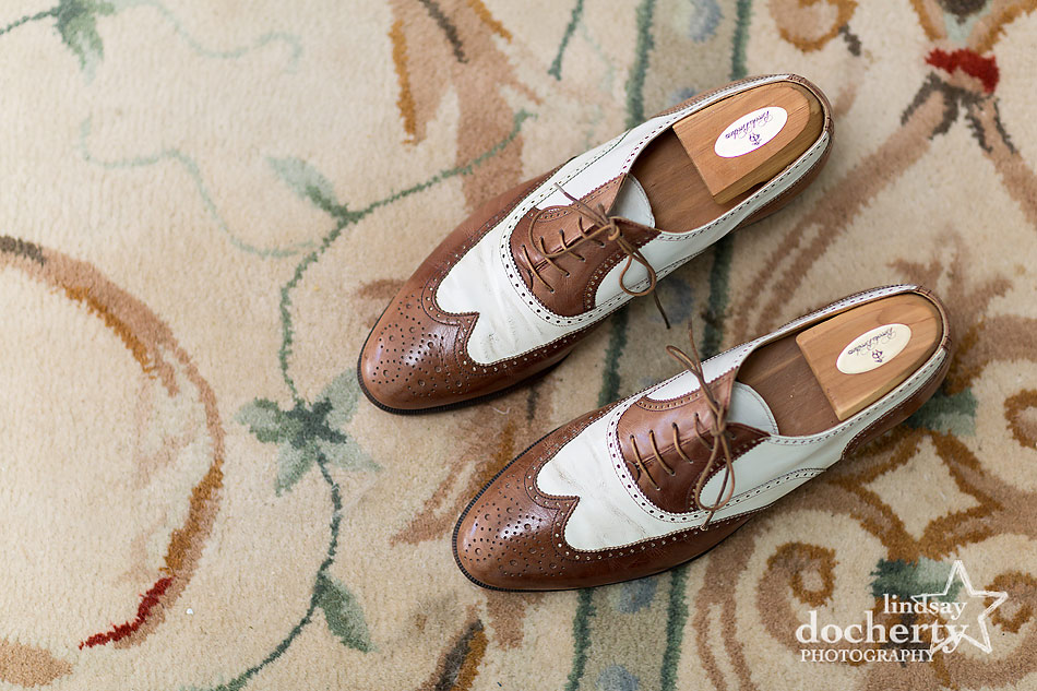 brown and white wingtip groom shoes