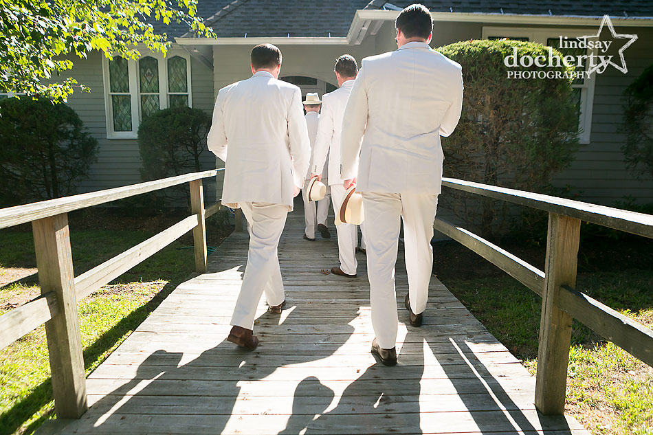 groomsmen in tan suits and blue shirts with sunglasses and hats for backyard wedding on Shelter Island, New York