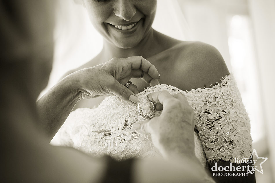 Greek bride getting ready for wedding day with family heirloom pin at backyard wedding on Shelter Island, New York
