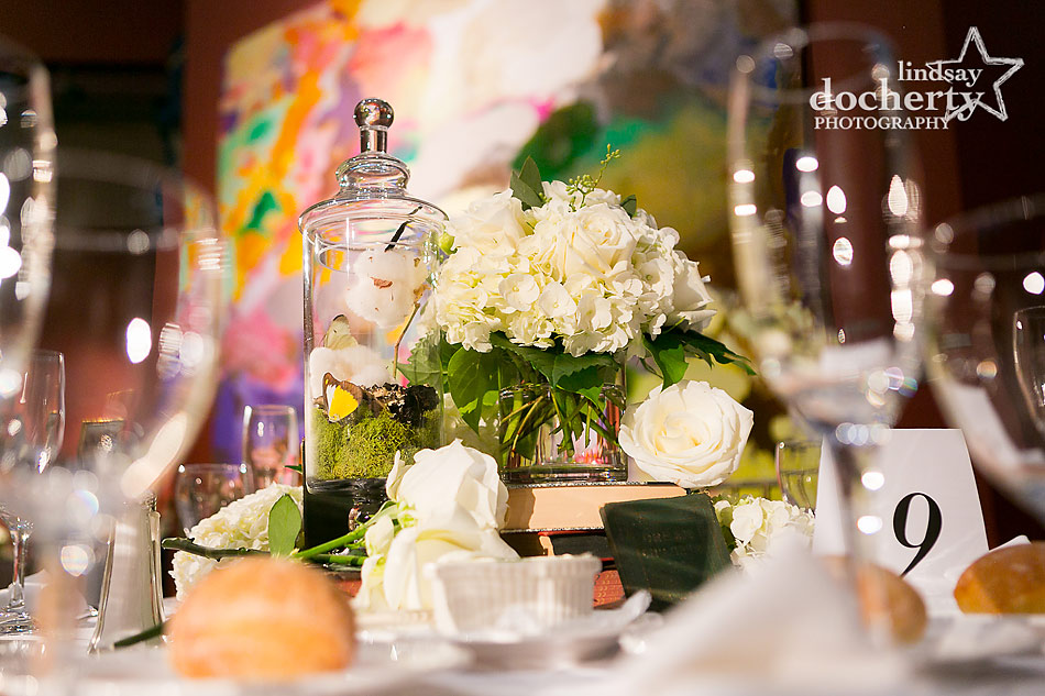 reception table with white flowers, cloches, cotton, butterflies, and books at PAFA wedding in Philadelphia