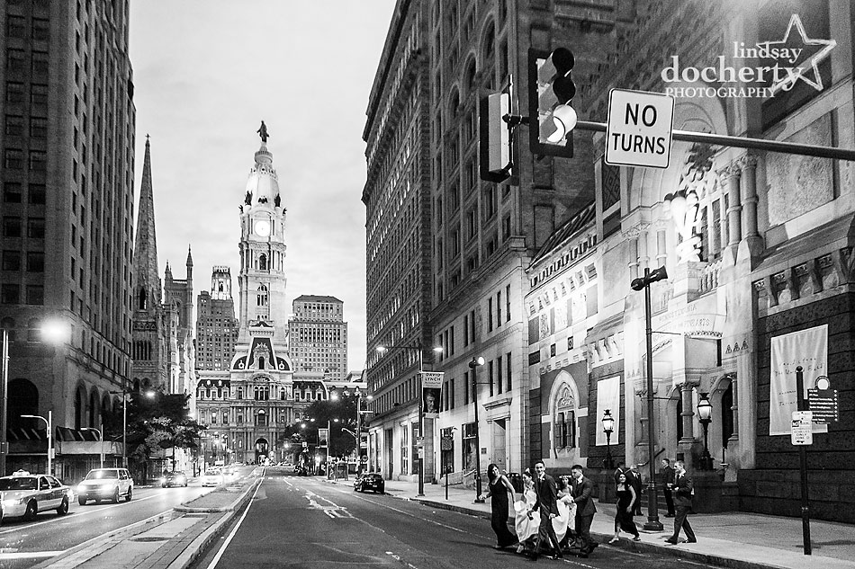 wedding party crossing Broad Street at night for Philadelphia picture with City Hall
