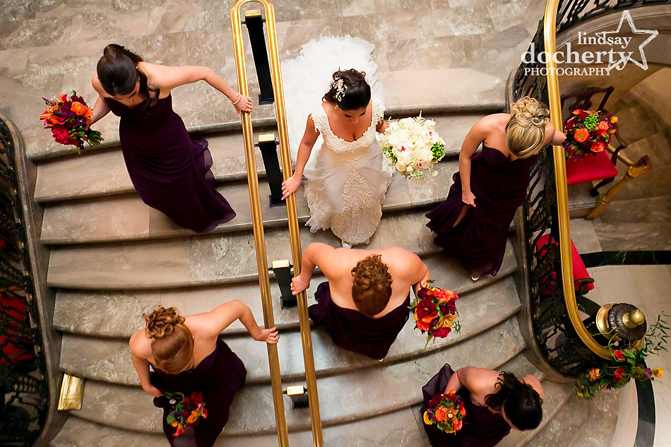 bride-and-bridesmaids-walking-down-stairs-at-hotel-dupont