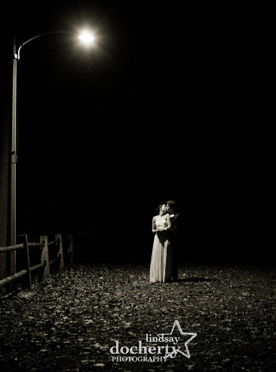 bride-and-groom-kiss-at-night-under-streetlamp-at-fall-Valley-Green-Inn-wedding-in-Philadelphia