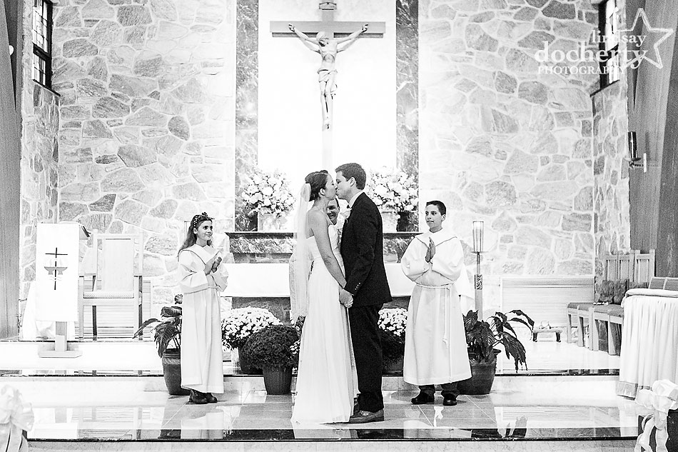bride-and-groom-kiss-at-wedding-ceremony-at-st-philip-neri-church-in-lafayette-hill