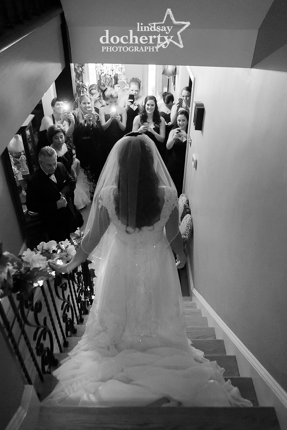 bride-walking-down-stairs-to-bridesmaids-and-family