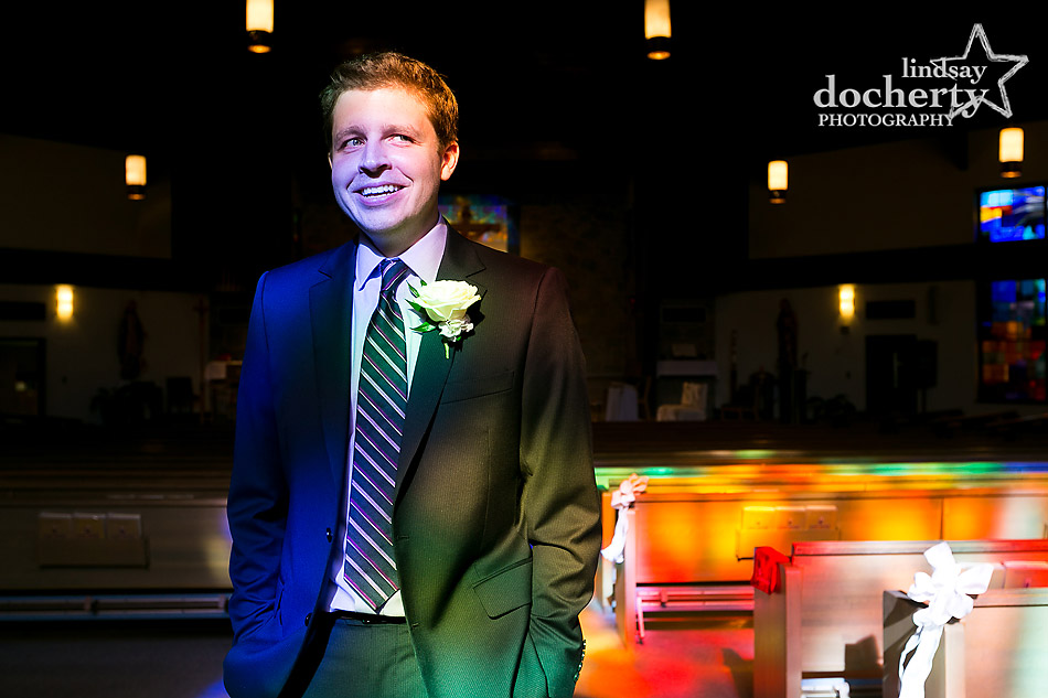 groom-with-colorful-stained-glass-church-window-before-wedding-ceremony