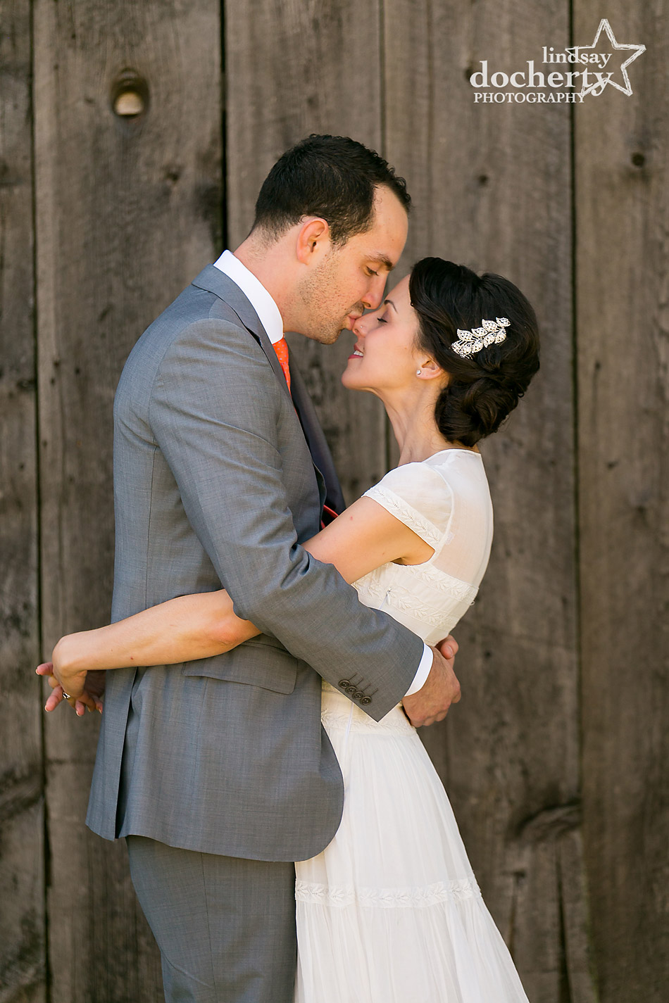 bride-and-groom-kissing-against-barn-wall-for-summer-wedding