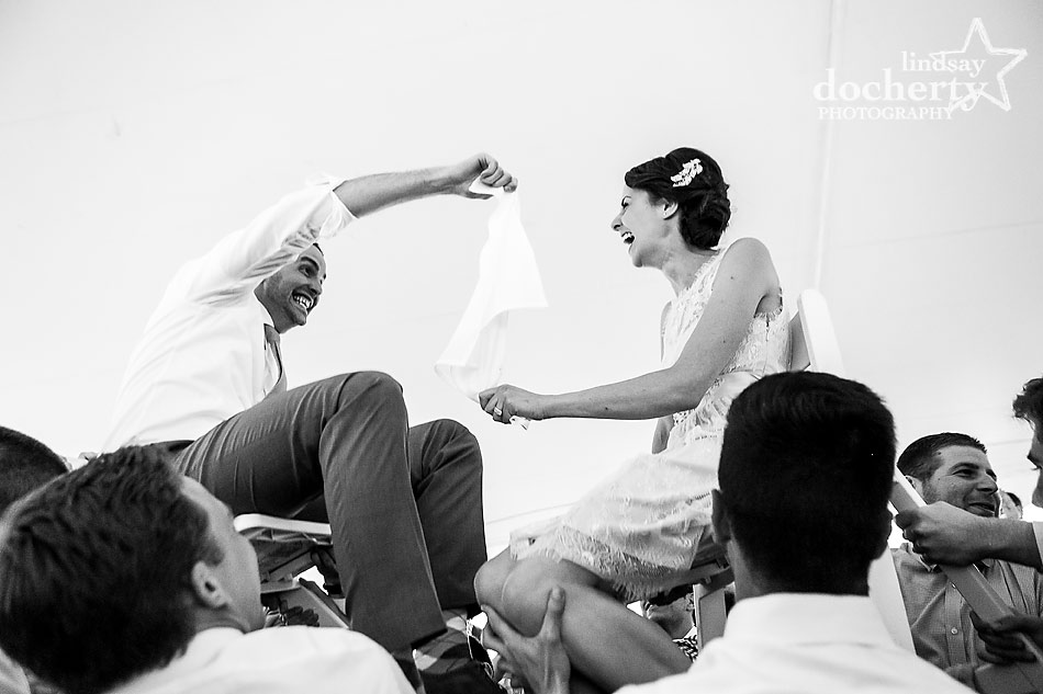 bride-and-groom-on-chairs-at-hora-at-Jewish-wedding-reception