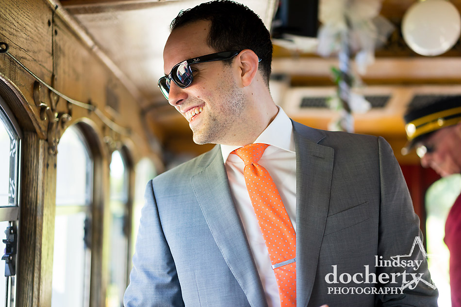 groom-in-sunglasses-on-trolley-on-way-to-wedding-ceremony