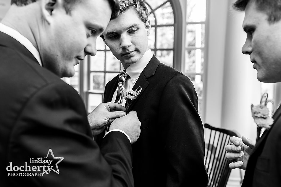 groom-putting-on-boutonniere-on-groomsmen-before-ceremony