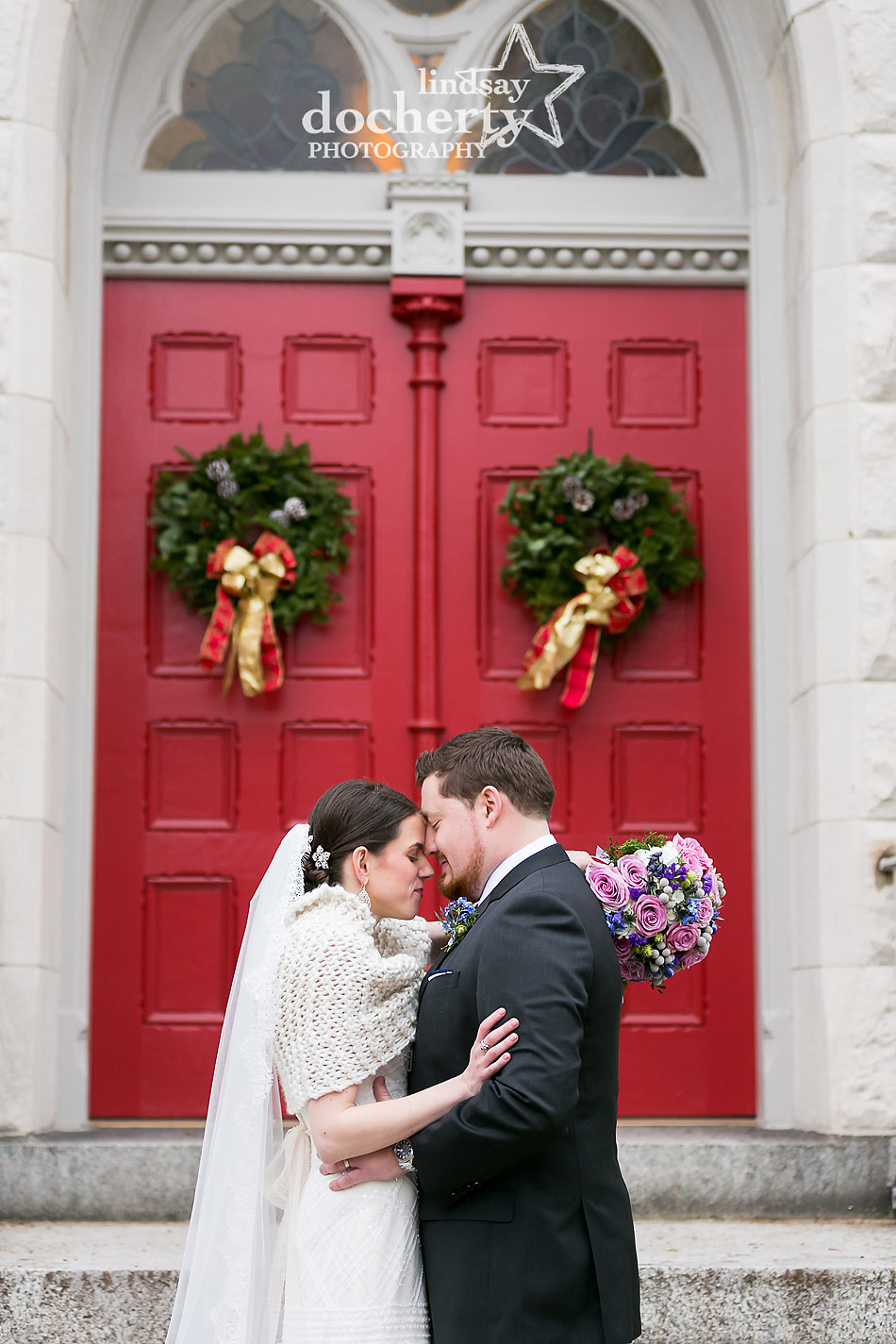 winter-wedding-with-bride-and-groom-in-front-of-red-church-doors