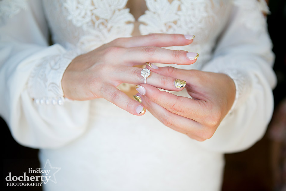 cushion cut engagement ring on bride with gold glitter nails and wedding dress with sleeves