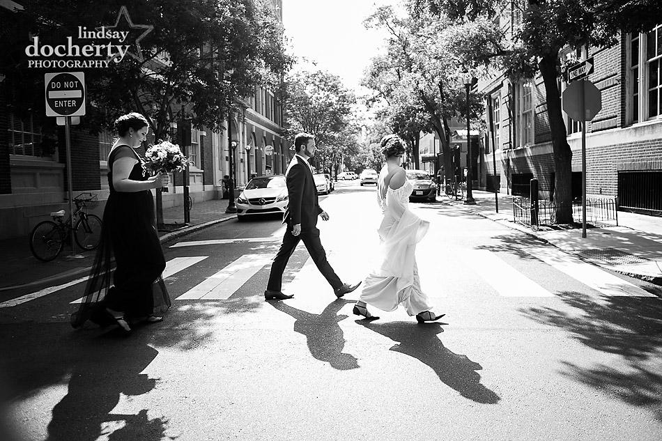 Philadelphia wedding photographer at Morris House Hotel walking across street with maid of honor