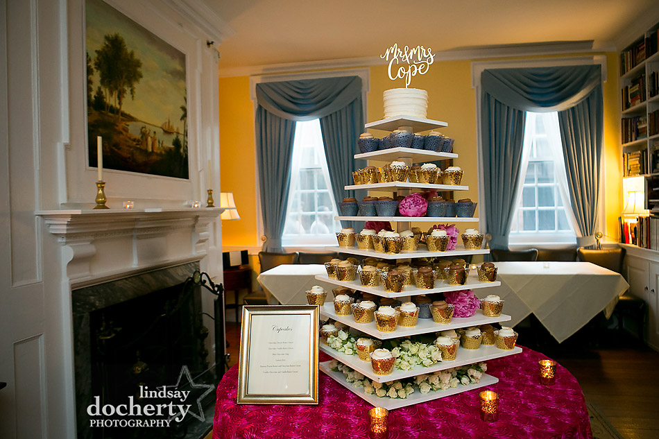 Philadelphia wedding photographer at Morris House Hotel flavored cupcake display with navy and gold wrappers