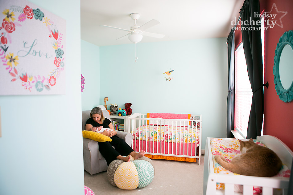 beautiful pink and blue nursery with cat, white crib, and Anthropologie pouf