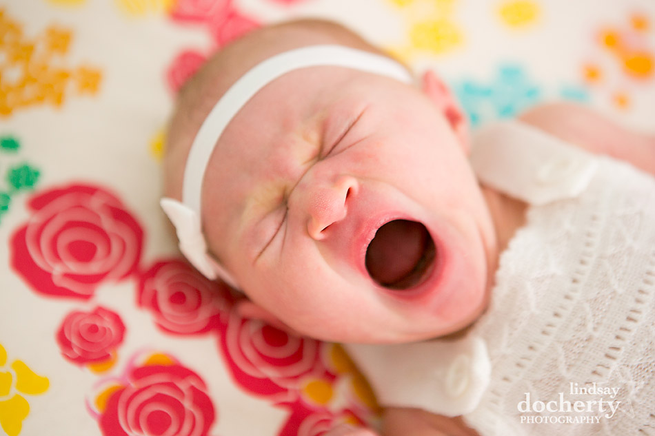 crying or yawning newborn baby girl on cute bedding