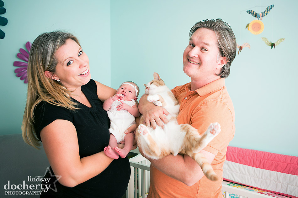 mom and dad holding newborn baby girl and pet cat in nursery at home