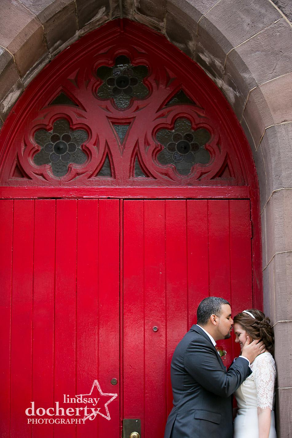 Philadelphia bride and groom kissing in front of red church door