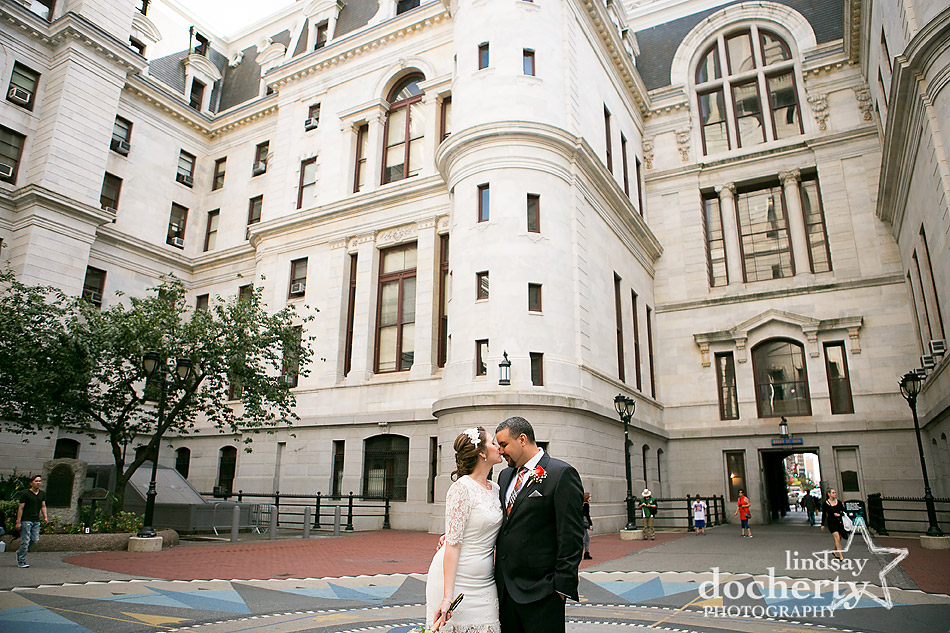 bride and groom kissing in middle of Philadelphia City Hall after wedding ceremony