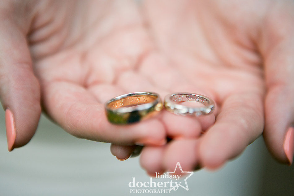 bride holding wedding bands with custom engraving