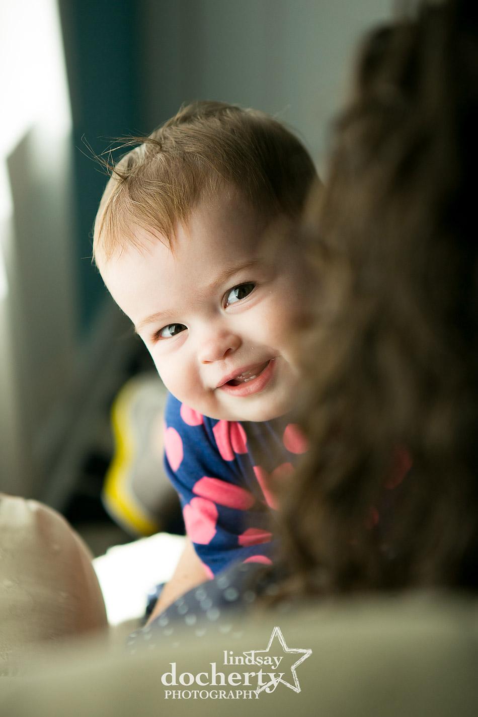 baby peekaboo behind mommy