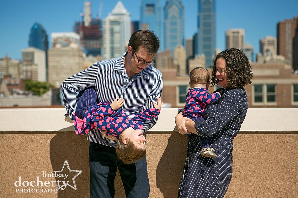 family on roofdeck with Philadelphia skyline
