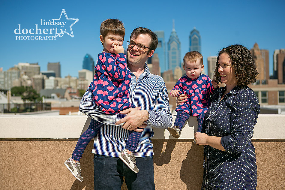 family with two girls on roofdeck in Philadelphia with skyline