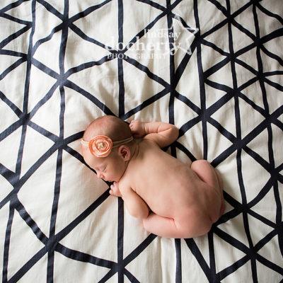 naked newborn baby girl on modern striped bed in Philadelphia