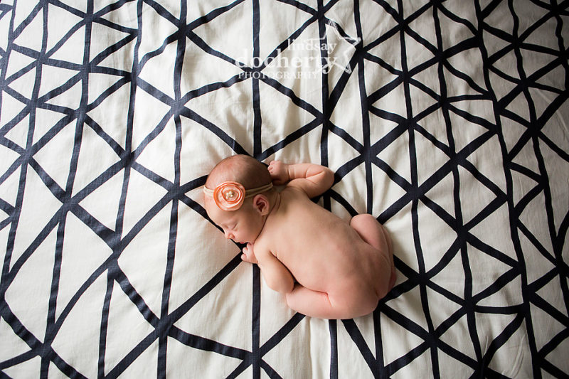 naked newborn baby girl on modern striped bed in Philadelphia